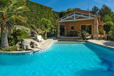 Populär villa med fin pool kantad av palmer, perfekt för familjer