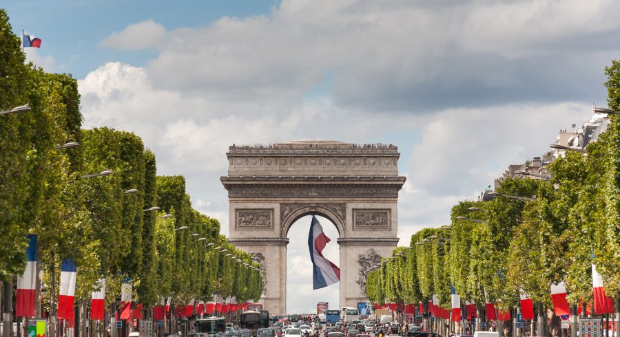 Arc de Triomphe viewed up the Champs Elysees and a large french flag flying under the arch