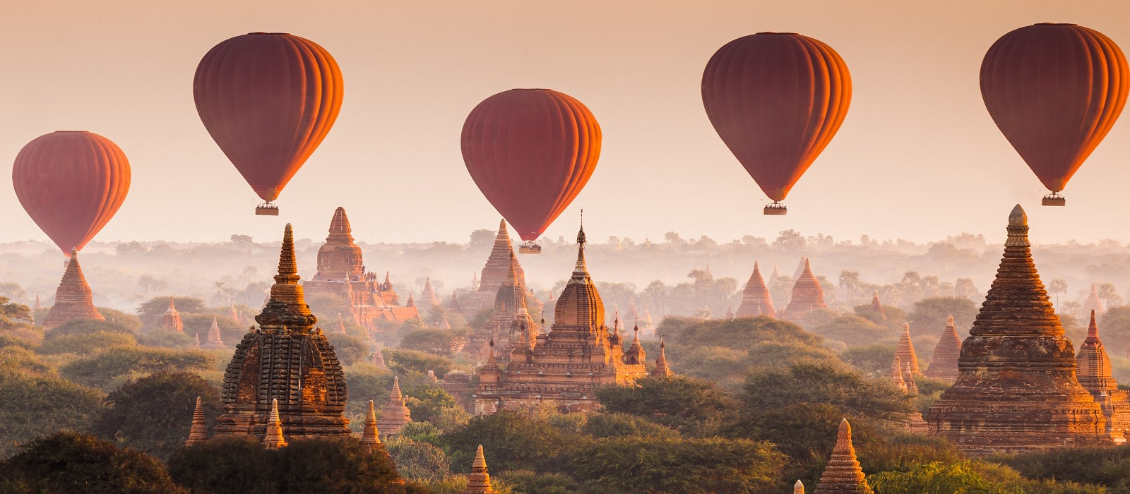 Mehrere rote Heißluftballons schweben über Bagan in Myanmar
