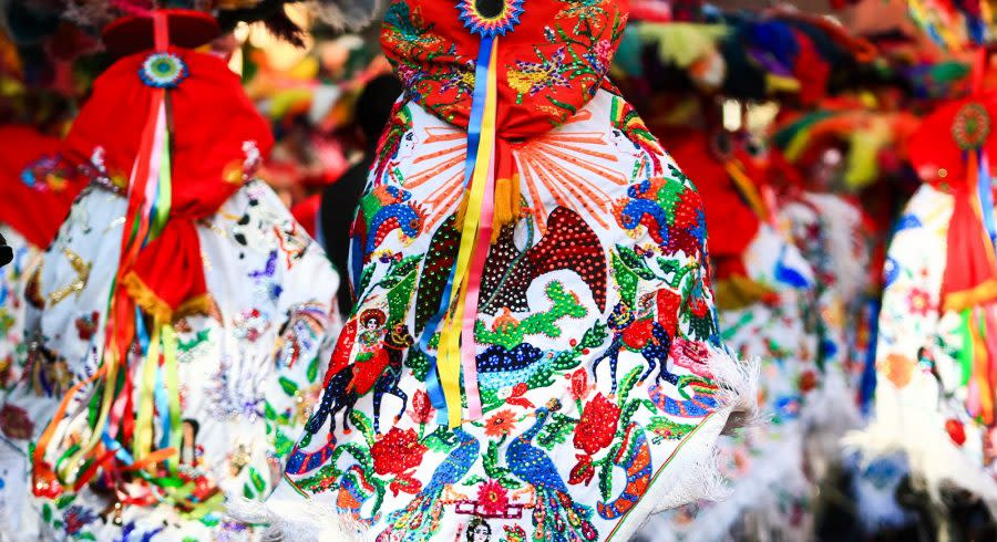 Enchanting Travels Mexico Tours Horizontal photo of a Carnival scene, dancers wearing a traditional mexican folk with an amazing cape rich in color
