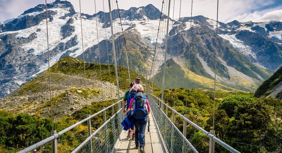 Amazing Nature of Hooker Valley Track in Mount Cook, New Zealand. Young Family walk on Suspension Bridge