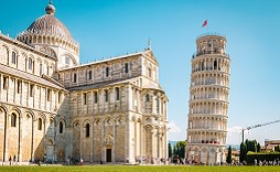 Enchanting Travels Italy Tours Leaning tower of Pisa, Italy with Basilica and Cathedral on a bright summer day with green gras low angle