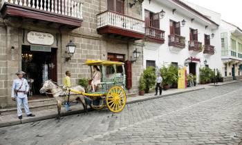 a man riding a horse drawn carriage on a street