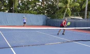 a couple of people on a court with a racket