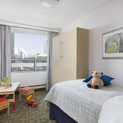 a bedroom with a stuffed animal sitting on a bed