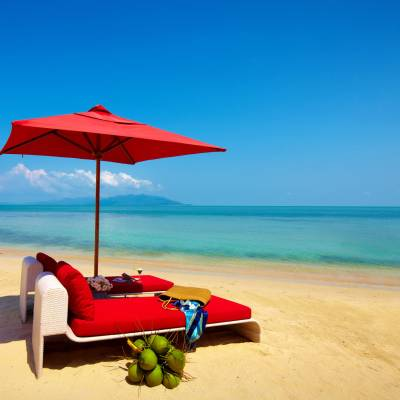 a red umbrella sitting on top of a beach