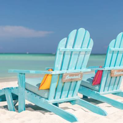 a couple of lawn chairs sitting on top of a beach