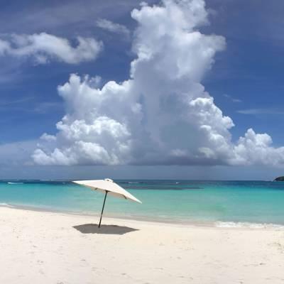 a blue umbrella sitting on top of a sandy beach