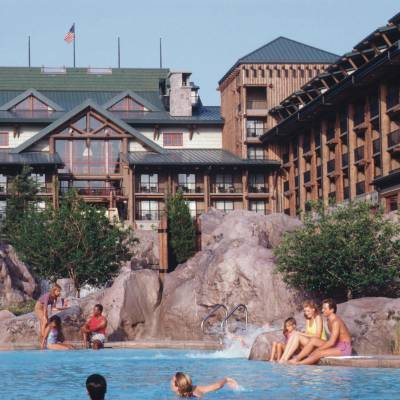 a group of people in a swimming pool with Disney's Wilderness Lodge in the background
