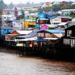 Bunte auf Pfählen gebaute Häuser am Ufer, Isla Grande de Chiloé, Chile