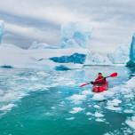 Einzelner Kajakfahrer inmitten von Eisbergen