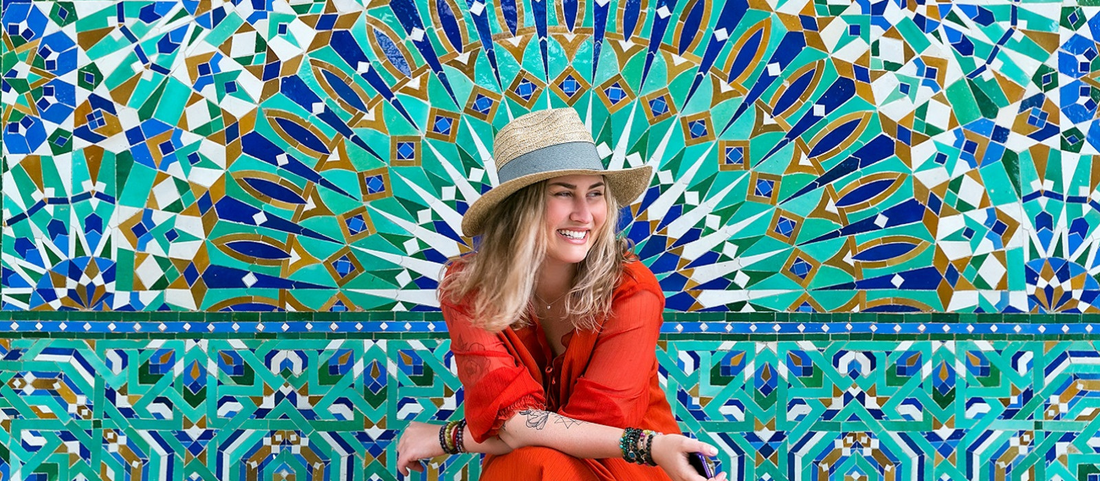 Enchanting Travels Morocco Tours Young blond woman in hat and in red dress is sitting on a multicolored mosaic wall background and smiling happily