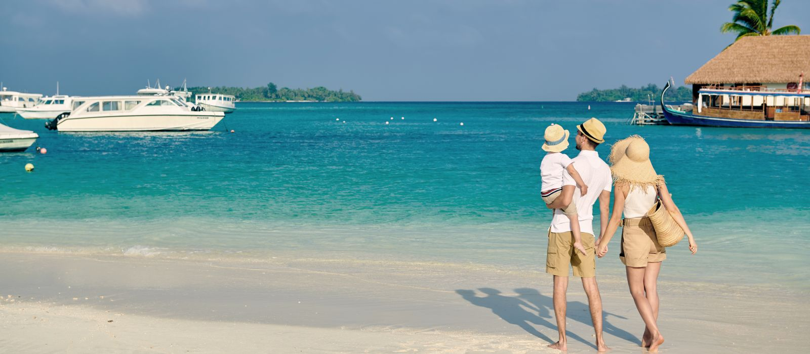 Family on beach, young couple with three year old boy. Summer vacation at Maldives