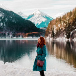 Young redhead girl in coat near lake in Alps, Germany Tours