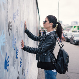 Enchanting Travels Germany Tours Young woman in front of Berlin Wall - German History
