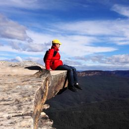 Sitting on Top of the World - hiker rests high on a cliff ledge and admires views of Blue Mountains on a beautiful sunny day.