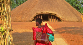 Frau in bunter Kleidung steht vor reetgedecktem Haus in Kampala, Uganda, Afrika