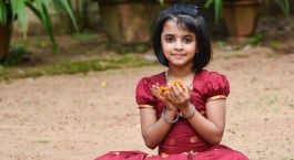 Girl holding flower in hand during Onam Festival Kerala Tour