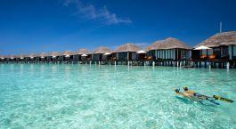 Zwei Taucher im türkisfarbenen Wasser vor reetgedeckten Villen des Hotels Velassaru Maldives auf Stelzen, Malediven