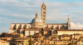 Enchanting Travels Italy Tours City view of Siena in the evening light in summer