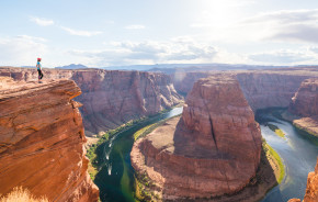 Woman stands over Horseshoe Bend, Grand Canyon