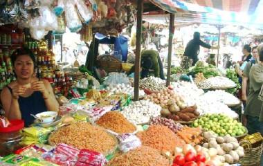 Straßenmarkt in Vietnam mit Verkäuferin und unzähligen Gemüsesorten und Gewürzen