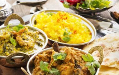 Schälchen von indischen Gerichten wie Curry, Reis und Naan