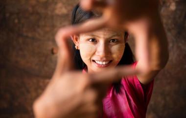 Schöne junge Frau aus Myanmar lächelt spielerisch in die Kamera