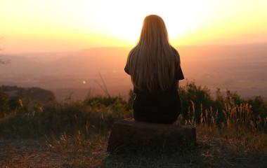 Frau beobachtet den Sonnenuntergang