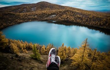 Blick hinunter auf idyllischen See inmitten bergiger Wälder
