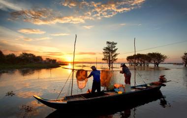 Zwei Männer im Boot leeren die Netze