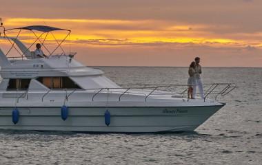 Junges Paar steht auf dem Deck einer Yacht bei Sonnenuntergang