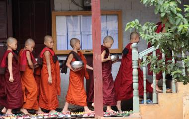 Eine Gruppe von jungen buddhistischen Mönchen geht die Treppe eines Hauses in Myanmar hinauf