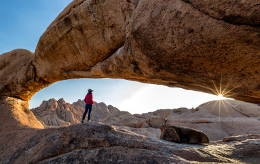 Nature reserve Spitzkoppe in Namibia. Picturesque stone arches are painted by iron oxides in red-orange color