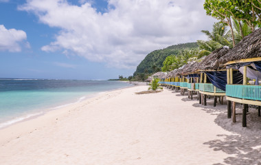 Samoa Tour: View along Lalomanu Beach, Upolu Island, Samoa, South Pacific, of thatched open-sided Samoan beach fale huts that are an alternative to hotel or resort accommodation