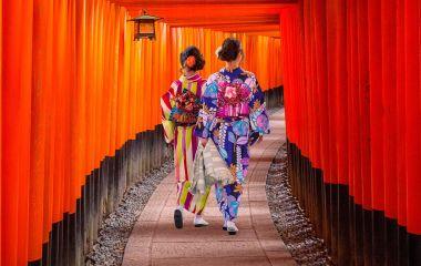 Top 10 temples in Japan - Women in traditional japanese kimonos walking at Fushimi Inari Shrine in Kyoto, Japan