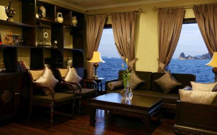 Klassisches Wohnzimmer der Halong Violet mit Sitzgruppe, dunklen Holzmöbeln und Blick auf die Halong-Bucht, Vietnma