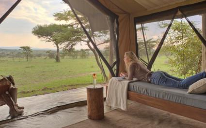 Frau liegt auf Bett und blickt auf die afrikanische Landschaft