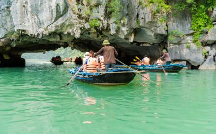 Mehrere Paddelboote unterqueren Felsen in der Halong-Bucht in Vietnam