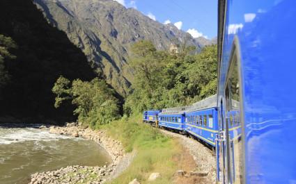 Blauer Zug fährt durch Gebirge von Cusco nach Machu Picchu, Peru