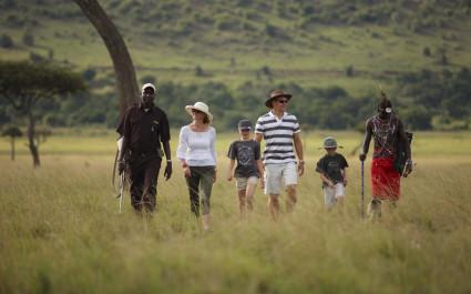 Touristen wandern mit Führer durch den afrikanischen Busch