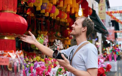 Tourist mit Kamera sieht sich eine rote Laterne in Chinatown an