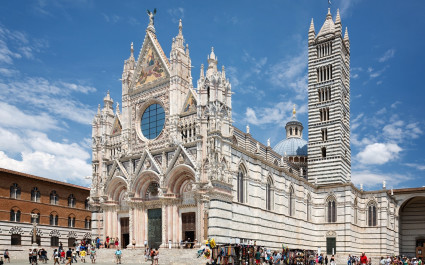 Siena cathedral against a bright blue sky in Italy