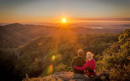 A young couple enjoying the beautiful sunrise on Mount Kaputar in New South Wales, Australia