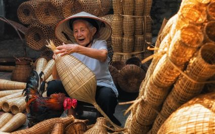 Enchanting TraOld Vietnamese female craftsman making the traditional bamboo fish trap