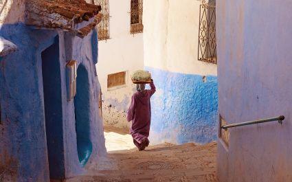 Frau im Gewand trägt etwas auf ihrem Kopf die Treppen in Chefchaouen, Marokko, hinunter