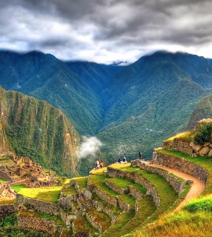 HDR-Panorama von Machu Picchu mit Terrassen, vereinzelten Besuchern und bewölktem Himmel in Peru