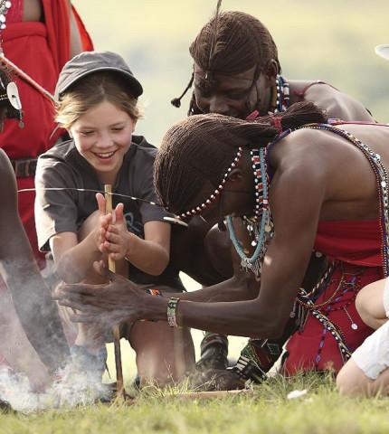 Vier traditionell gekleidete Männer der Massai in Kenia zeigen zwei kleinen Touristen, wie man eigenhändig ein Feuer entzündet