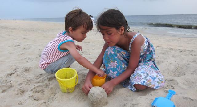 Ein kleiner Junge und ein kleines Mädchen spielen am Strand von Marari im Sand