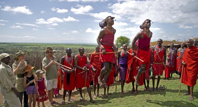Angehörige des Maasaistammes in traditionellen Kleidern mit Gästen von Enchanting Travels